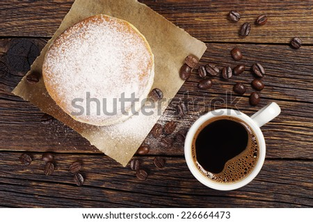 Cup of hot coffee and donut with powdered sugar on dark wooden table. Top view - stock photo