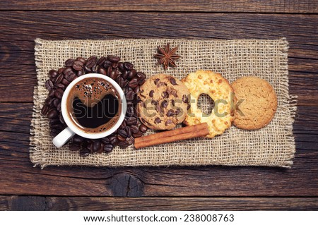 Cup of hot coffee and various sweet cookies on dark wooden table with burlap, top view - stock photo