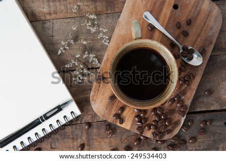 Cup of hot coffee and white note book on wood table background - stock photo
