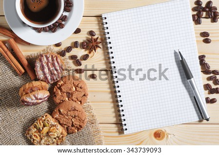 Cup of hot coffee, cookies and opened notepad on a wooden table, top view - stock photo