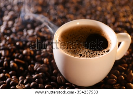Cup of hot coffee on coffee beans background - stock photo