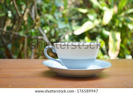 Cup of hot coffee on table in the garden - stock photo