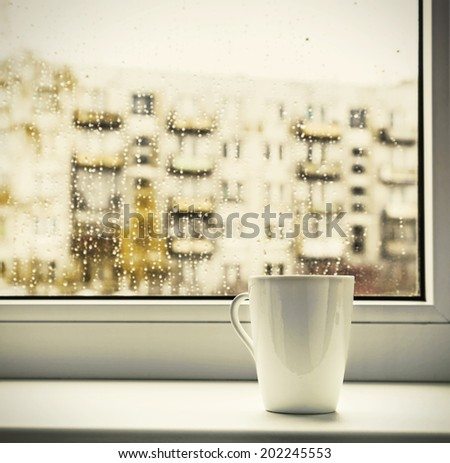 cup of hot coffee on the window sill wet from the rain. toning style instagram - stock photo