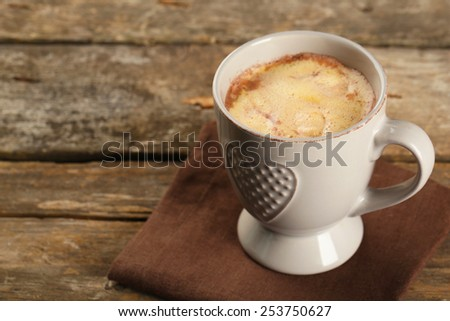 Cup of hot coffee with marshmallow on napkin and rustic wooden planks background - stock photo