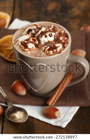 Cup of hot coffee with marshmallow on napkins with hazelnut, cinnamon and dried orange on rustic wooden planks background - stock photo