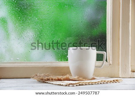 Cup of hot drink with napkin on windowsill on rain background - stock photo
