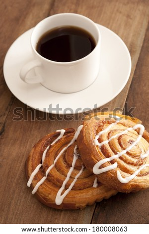 Cup of hot espresso coffee with fresh spiral buns decorated with vanilla icing served on a wooden counter top - stock photo