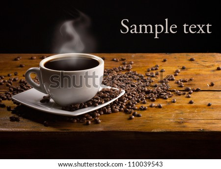 cup of hot espresso with coffee beans on dark wooden background - stock photo