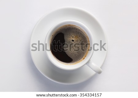 Cup of hot fresh black coffee with foam against white background. Coffee cup on round saucer centered inside frame. Top view with place for text. Concept of morning, energy and cheerfulness. - stock photo