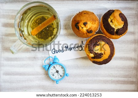 Cup of hot green tea, cupcakes and Good morning note on the wooden table - stock photo