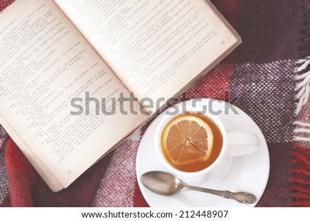 Cup of hot tea and reading on a blanket, instagram style toned. Top view point. - stock photo