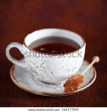 Cup of hot tea and rock candy sugar stick, selective focus - stock photo