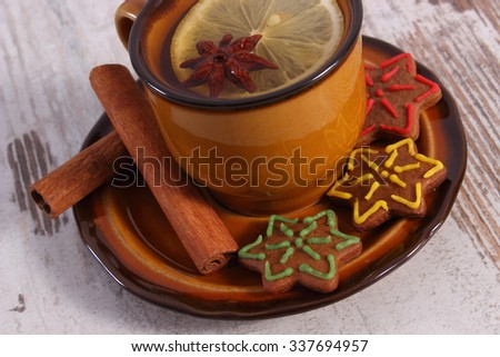 Cup of hot tea, fresh baked homemade decorated gingerbread or Christmas cookies, cinnamon sticks on old white wooden background, christmas time - stock photo
