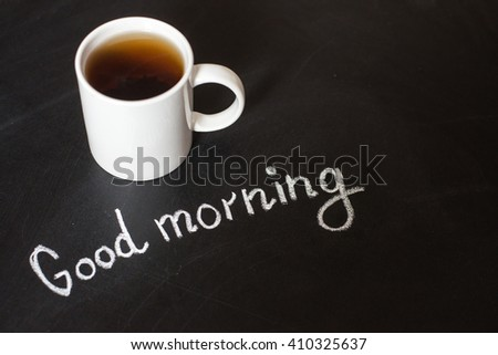 cup of hot tea on a black board and text good morning - stock photo