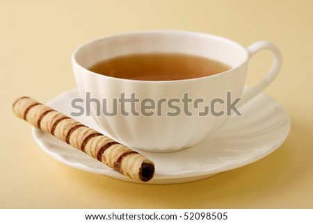 Cup of hot tea served in a white china teacup with Creme Roulee Cookies. - stock photo