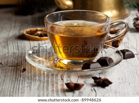 Cup of hot tea with dark chocolate on old wooden table - stock photo