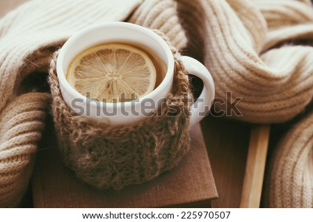 Cup of hot tea with lemon dressed in knitted warm winter scarf on brown wooden tabletop, soft focus - stock photo