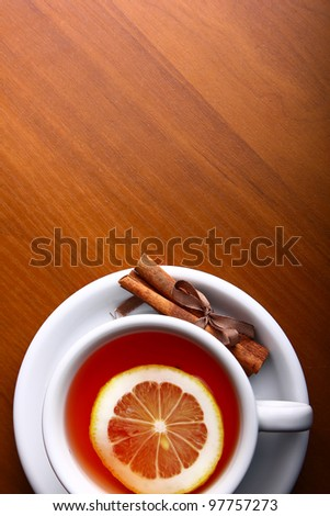 Cup of Hot Tea with Lemon on a wooden table - stock photo