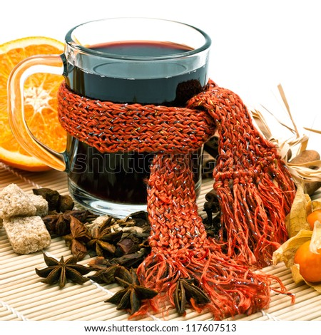 Cup of hot wine in scarf and spices on cane tray - stock photo