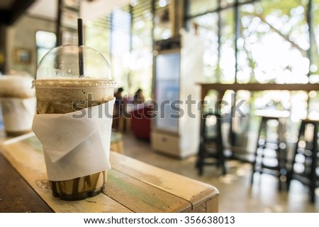 cup of Ice Caramel Macchiato and ice cappuccino on the wooden table in coffee shop blurry background - stock photo