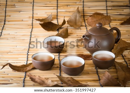 Cup of Jasmine tea, bamboo mat background - stock photo