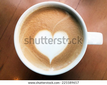 cup of latte art coffee on wood table in top view - stock photo