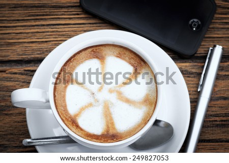 Cup of latte coffee with a pen and a smartphone, on wood - stock photo