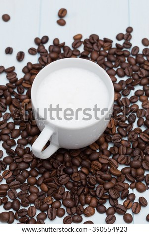 Cup of latte coffee with beans on wood table - stock photo