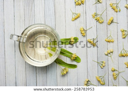 cup of lime tea and linden flowers, bright wooden table, high angle view - stock photo