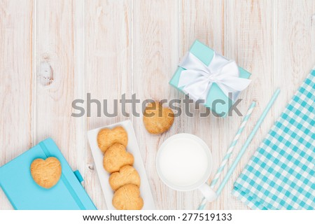 Cup of milk, heart shaped cookies, gift box and notepad on white wooden table with copy space - stock photo