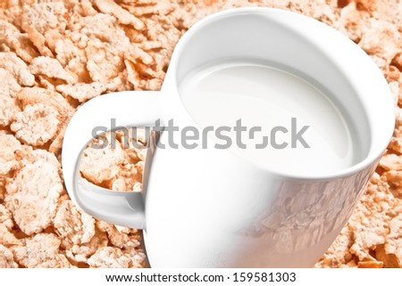 cup of milk on corn flakes background, nutrition concept - stock photo
