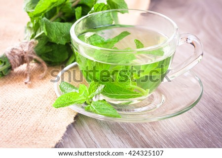 Cup of mint tea and a bunch of mint on the table - stock photo