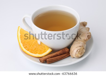 Cup of orange tea with cinnamon and ginger on white background. Shallow dof - stock photo