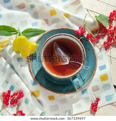 Cup of organic black tea with tea bag in it, set with red currant on brightly lit wooden table, outdoor natural light setting, toned photo. - stock photo