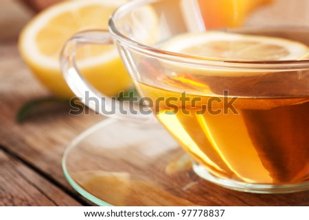 Cup of organic  lemon fruit tea on nature wooden background - stock photo