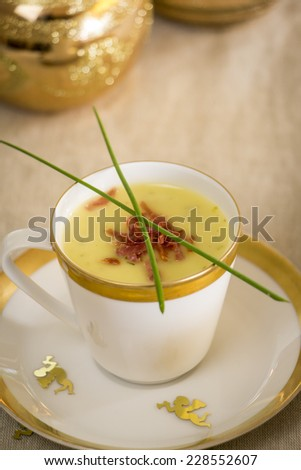 Cup of potato and ham soup garnished with serrano peppers served as an appetizer for Christmas dinner with gold trim and golden Xmas candles burning in the background as table decoration - stock photo