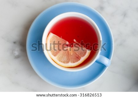 Cup of red fruit tea with lemon slice, top view - stock photo