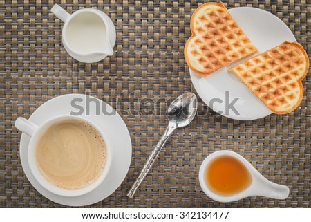 Cup of steaming coffee and a fresh waffle - stock photo