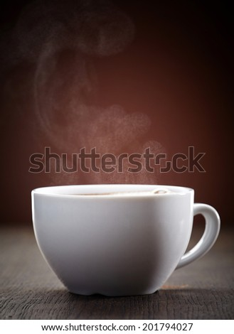 cup of steaming  coffee on brown wooden table, soft focus - stock photo