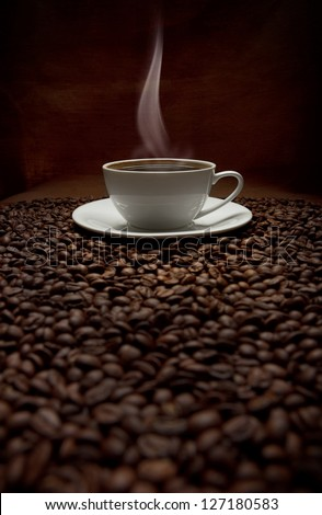 cup of steaming coffee with beans - stock photo