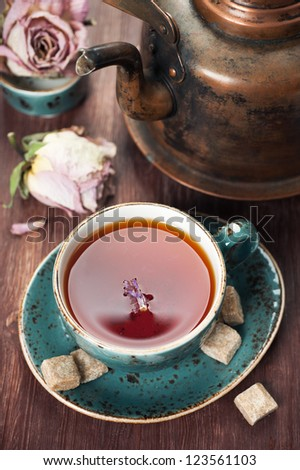 Cup of tea and a vintage teapot - stock photo