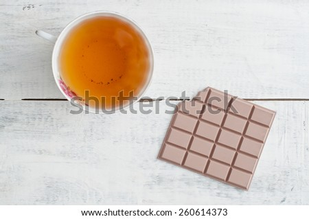Cup of tea and bar of milk chocolate on white wooden table - stock photo