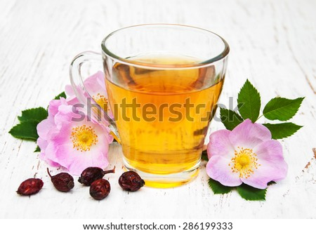 Cup of tea and dogrose on a old wooden background - stock photo