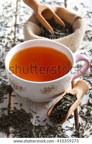 Cup of tea and dried tea leaves - stock photo