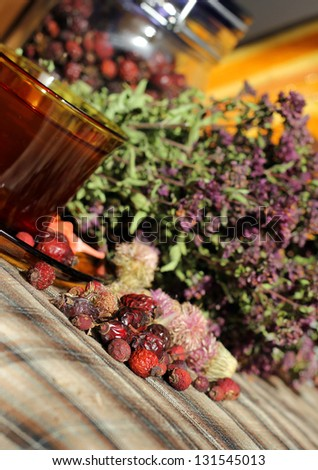 Cup of tea and hawthorn, oregano, hip and other herbs on the table - stock photo