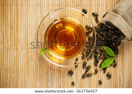 Cup of tea and leaves tea on wooden placemat - stock photo