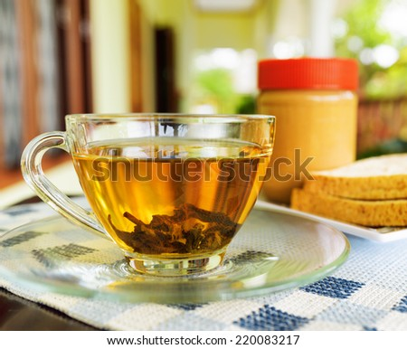 Cup of tea and peanut butter. Breakfast on summer terrace. - stock photo