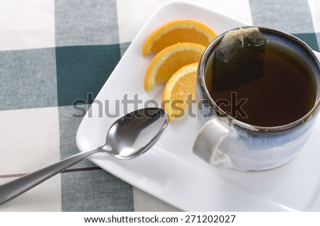 Cup of Tea and Spoon with Orange Slices on a Plaid Table Cloth - stock photo