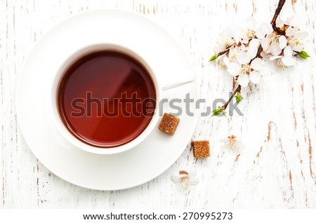 Cup of tea and spring apricot blossom on a wooden background - stock photo