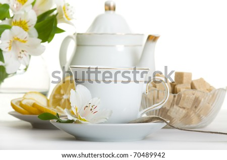 Cup of tea and teapot on table with flowers isolated over white - stock photo
